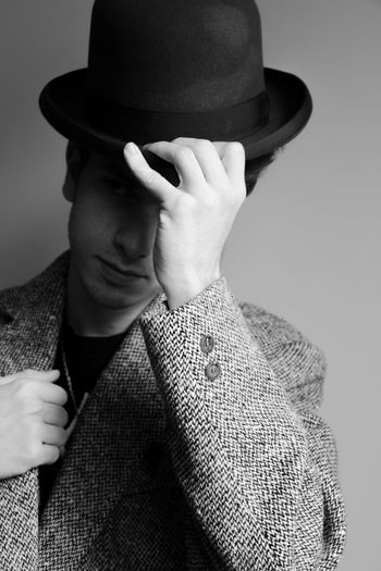Man wearing hat against wall
