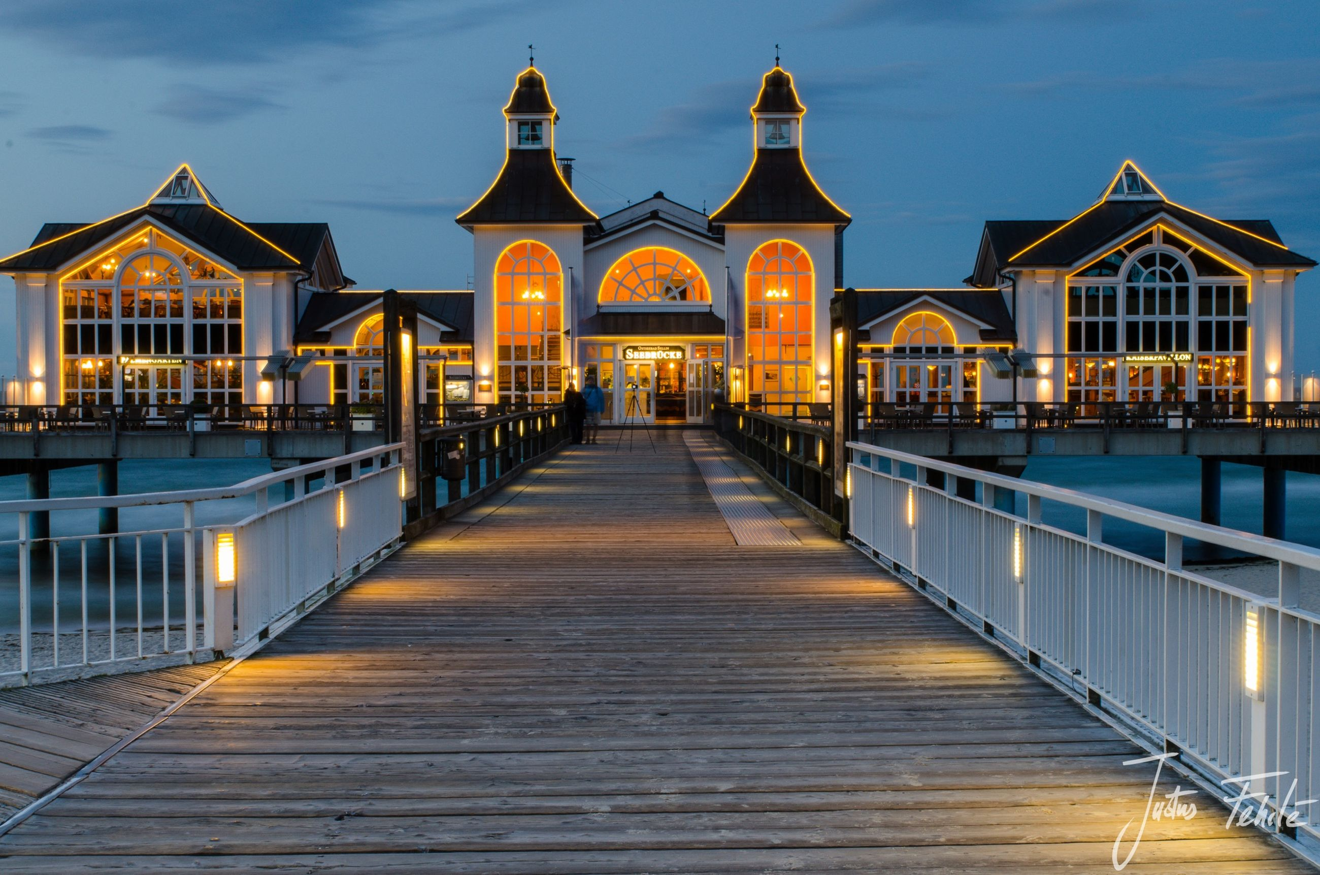 architecture, built structure, building exterior, the way forward, sky, railing, street light, illuminated, water, diminishing perspective, arch, in a row, outdoors, architectural column, incidental people, facade, reflection, no people, pier, travel destinations