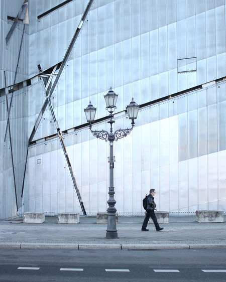 Man walking on street against buildings in city