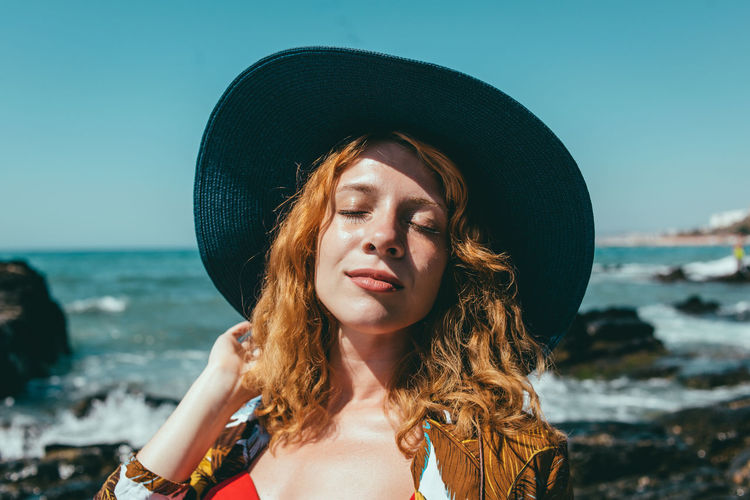 Portrait of young woman wearing hat at beach