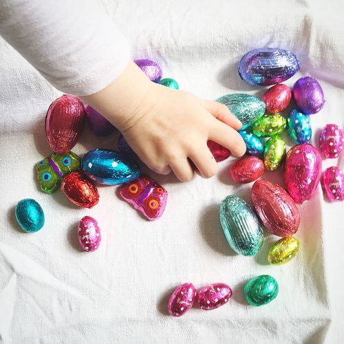 Small girl playing with multi colored egg-shaped candies