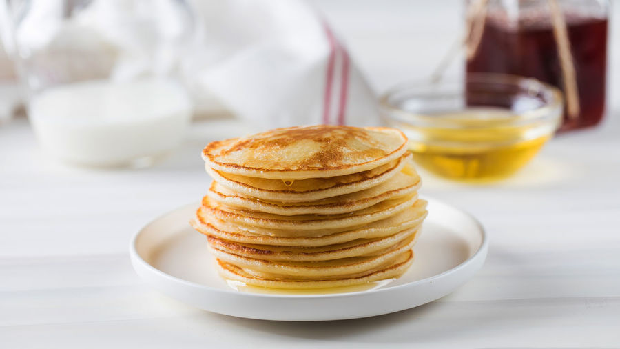 The pancakes are stacked in a plate. in the background, a bowl of honey and a jug of milk.