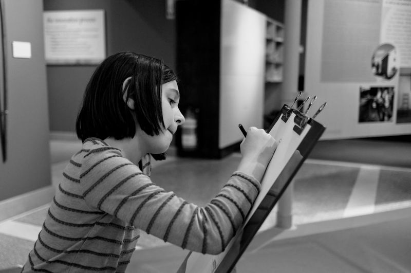 Girl Drawing On Clipboard At Museum