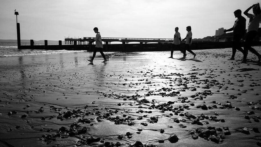 Let's go into the water Holiday Day Beach Life Light And Shadow Outdoors People Watching Blackandwhite Black And White Shadow Kids Sunset Eye4photography  Beachphotography Sand Life Is A Beach Beach Pier Nature Ocean Ocean View Bournemouth Stones & Water Stones Shadows Doing Sport