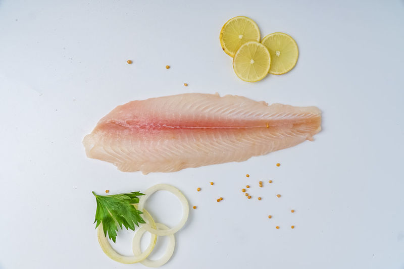 Directly above shot of fish and fruits on white background