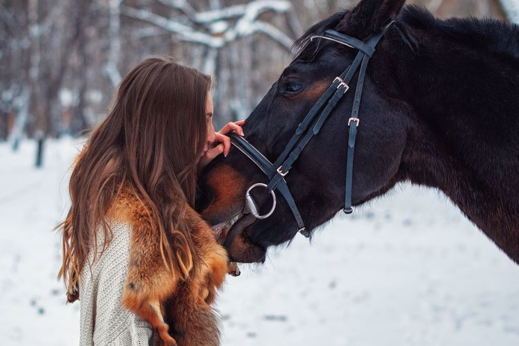 Close-up of woman with horse on snow