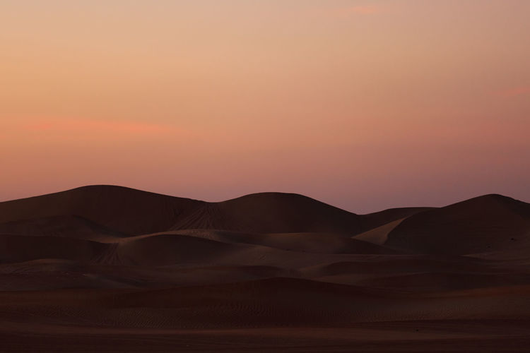 Sunset at the Desert of Dubai Scenics - Nature Sunset Sky Tranquility Beauty In Nature Tranquil Scene Desert No People Land Mountain Non-urban Scene Environment Landscape Orange Color Nature Sand Dune Sand Physical Geography Remote Idyllic Arid Climate Outdoors Climate Dubai Desert Safari