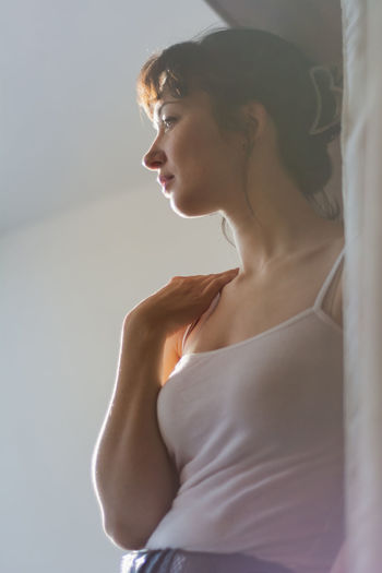 Low angle view of woman looking away while standing at home