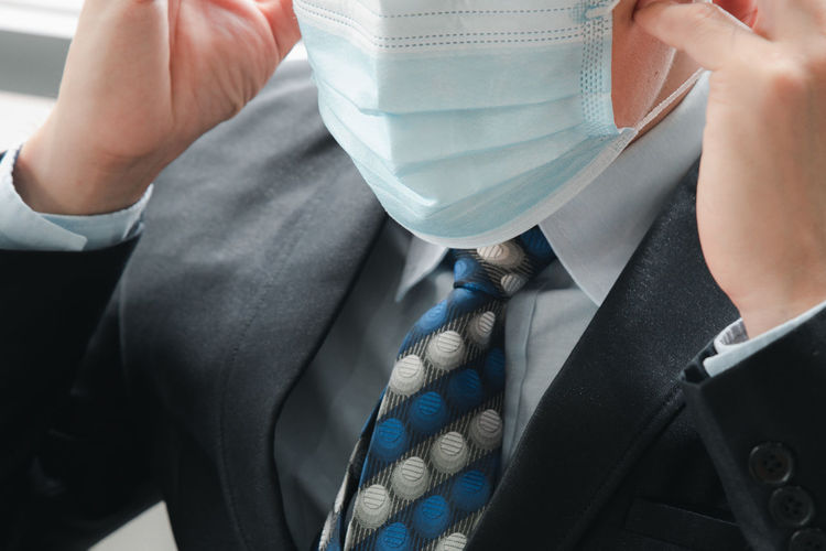 Midsection of businessman wearing mask