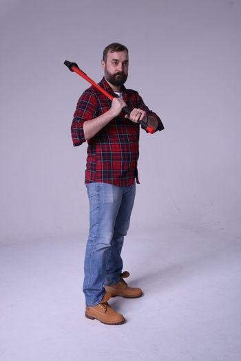 Full Length Of Lumberjack Holding Axe While Standing Against White Background
