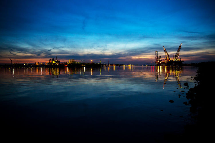 Copy Space Industrial Port Nightphotography Architecture Blue Built Structure Cloud - Sky Construction Equipment Crane - Construction Machinery Dusk Fuel And Power Generation Illuminated Industry Machinery Nature No People Outdoors Port Reflection Sea Sky Sunset Water Waterfront