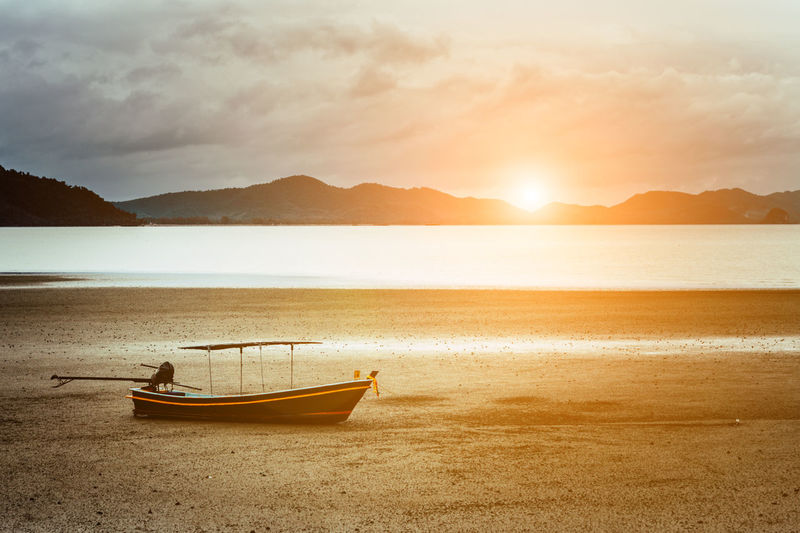 Beach Beauty In Nature Cloud - Sky Fishing Boat Land Mode Of Transportation Moored Mountain Mountain Range Nature Nautical Vessel No People Outdoors Rowboat Scenics - Nature Sea Sky Sun Sunset Tranquil Scene Tranquility Transportation Water