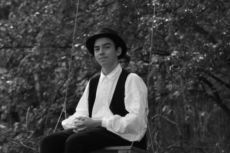 Portrait of teenage boy sitting on swing against plants