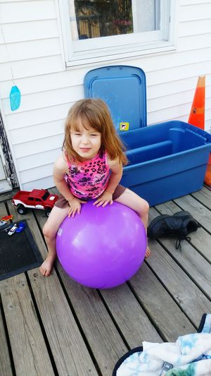 What a face!! Childhood Girls Lifestyles Leisure Activity Sitting Person Casual Clothing Cute Innocence Playing Full Length Looking At Camera Day Long Hair Outdoors Purple Ball Girl Playing With A Ball. Ball. At Home Big Ball. Cute Girl Girly Bouncing On Ball. Sitting On Ball. fresh on EyeEm