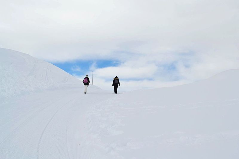 Rear view of people walking on snow covered hill against cloudy sky