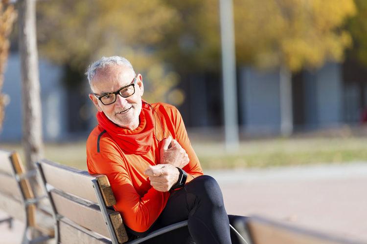 Portrait of smiling senior man sitting on bench in park