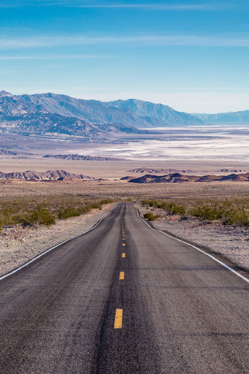 Looking down a road leading into death valley in california, with salt flats in the distance