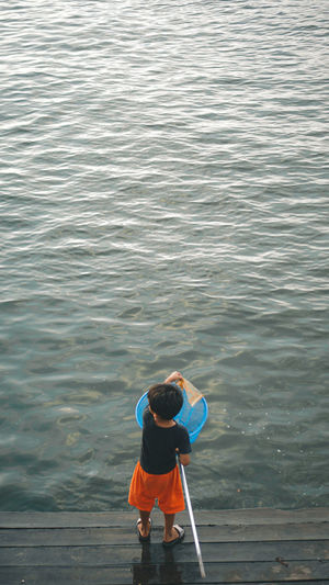 Rear view of man standing in sea child cleaning a trash