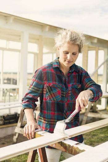 Happy girl working on wood
