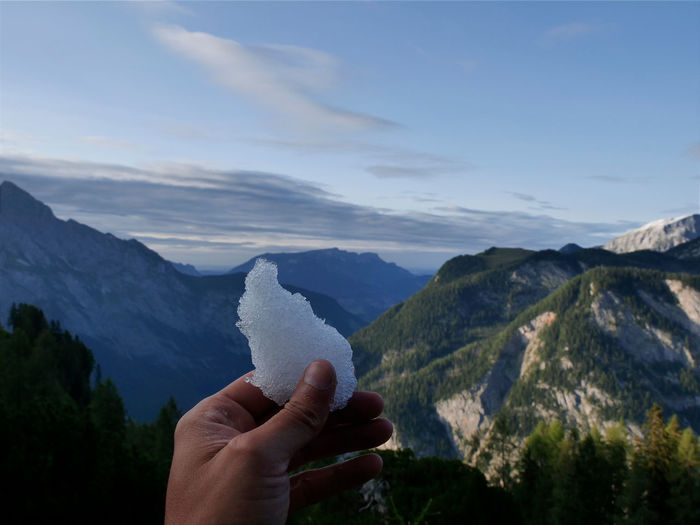 Cropped hand holding ice against mountain range