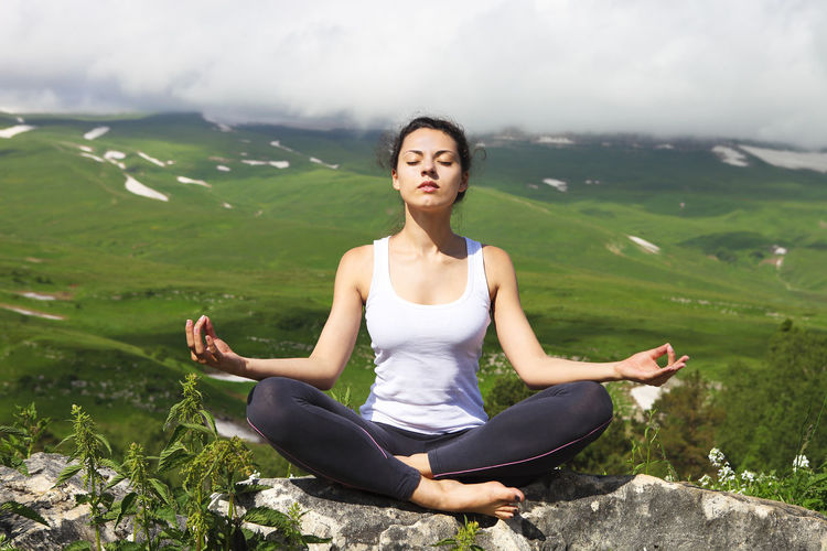 Young woman sitting on green landscape against mountains