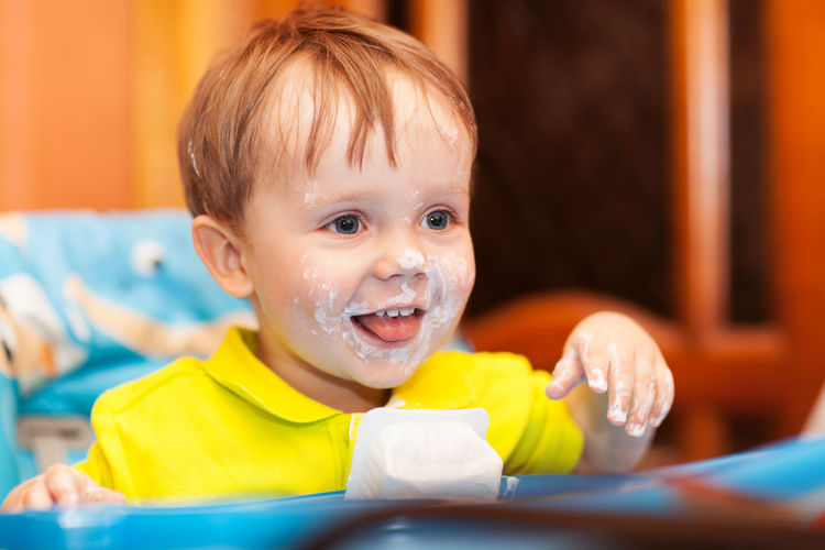 Close-up of happy boy with yogurt on face