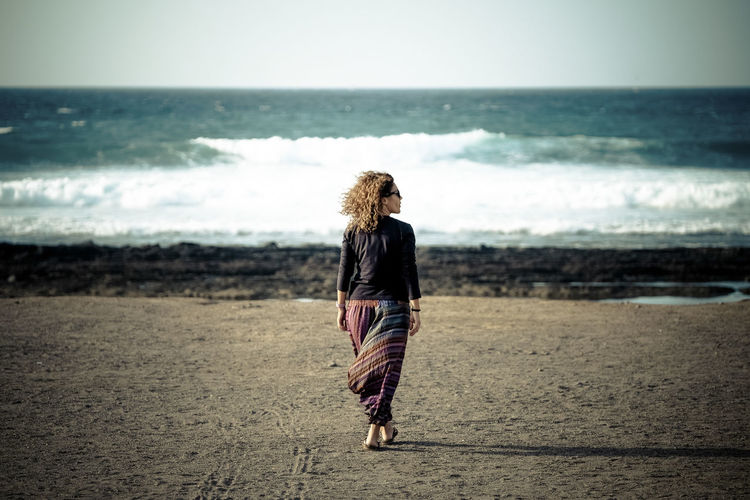 One woman walking at the beach to the ocean and waves enjoying the feeling of freedom and nature with wind in the curly hair - people in outdoor vacational activity Sea Beach Land Full Length One Person Water Horizon Over Water Horizon Walking Beauty In Nature Sky Casual Clothing Rear View Hair Real People Nature Women Scenics - Nature Hairstyle Outdoors Waves Hippie One Woman Only Caucasian Atlantic