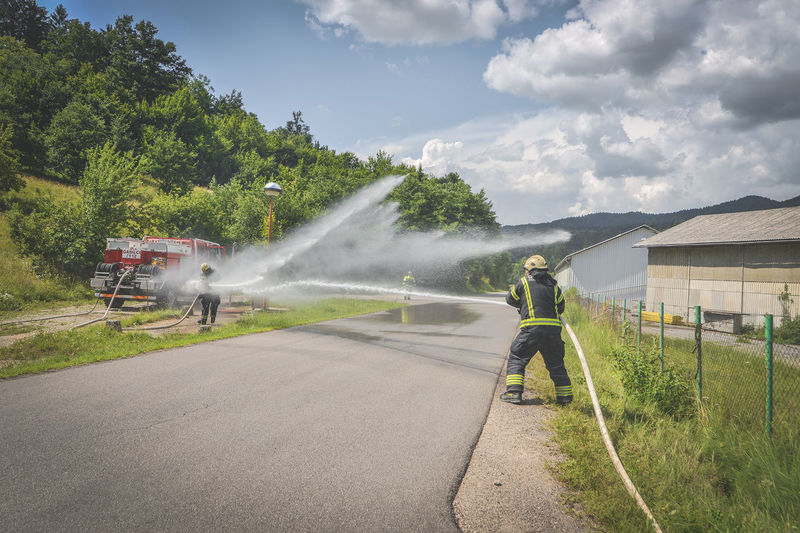 Firefighter spraying water on road against cloudy sky