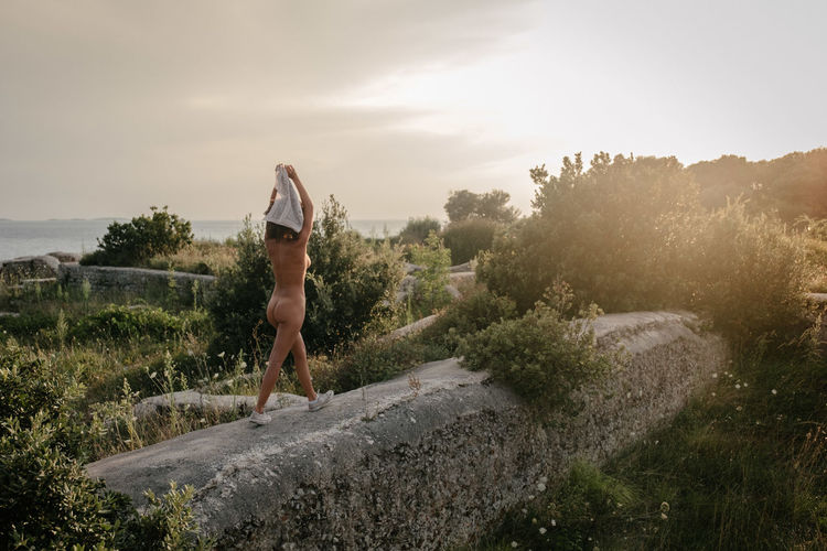 Naked Woman Walking On Railing Against Sky During Sunset