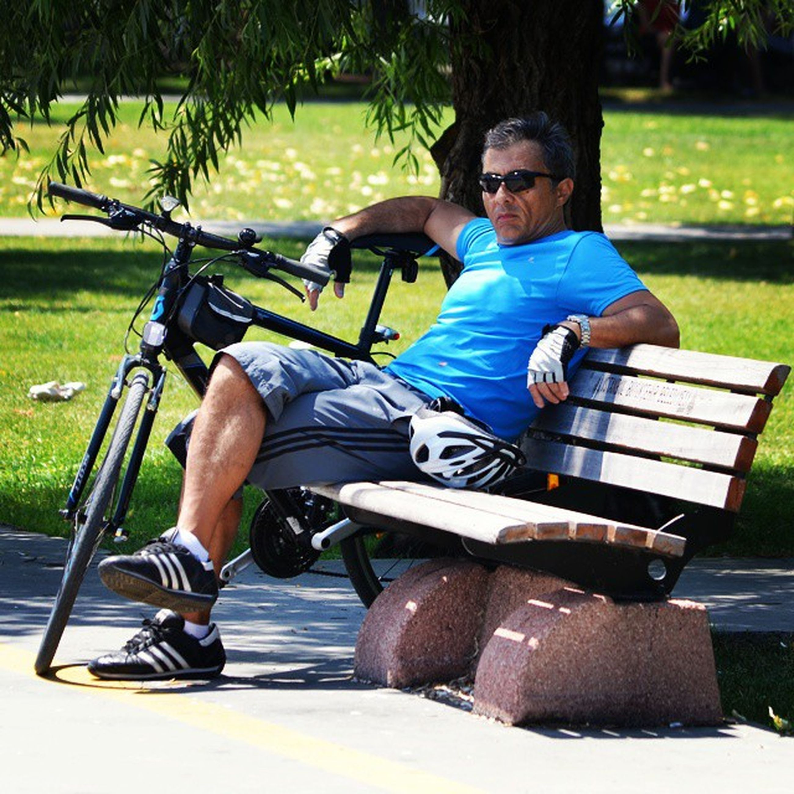 lifestyles, sitting, leisure activity, tree, relaxation, park - man made space, casual clothing, grass, full length, bench, chair, person, park, sunlight, young adult, day, childhood, outdoors