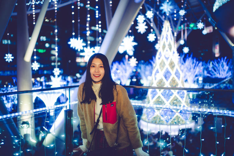 Portrait of young woman standing against illuminated lights at night