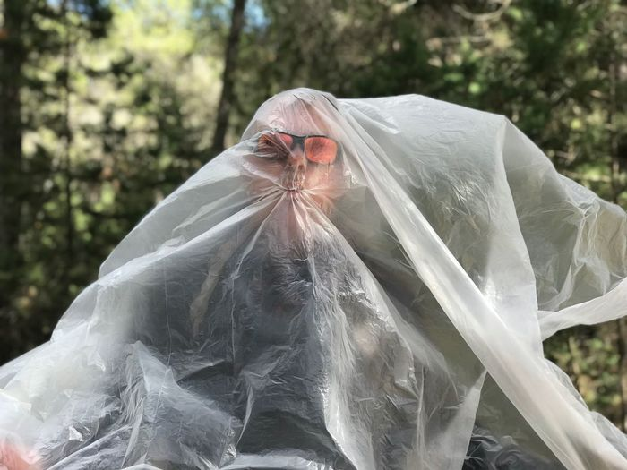 Mature man covered with plastic at park