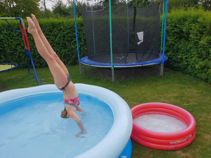 Full Length Of Girl Doing Handstand In Wading Pool