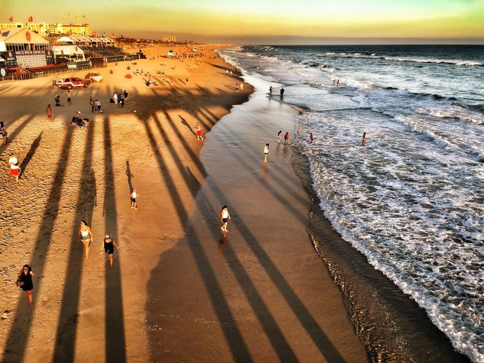High Angle View Of People On Shore At Beach During Sunset