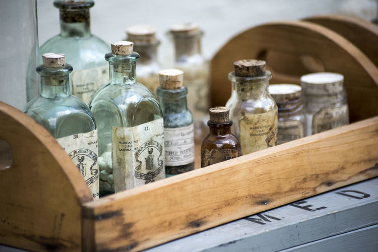 Close-Up Of Bottles In Wooden Tray