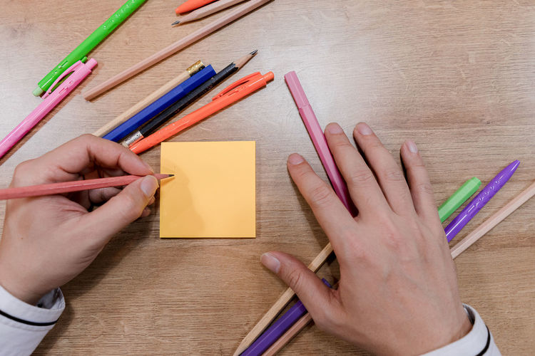 High angle view of hand holding pencils on table