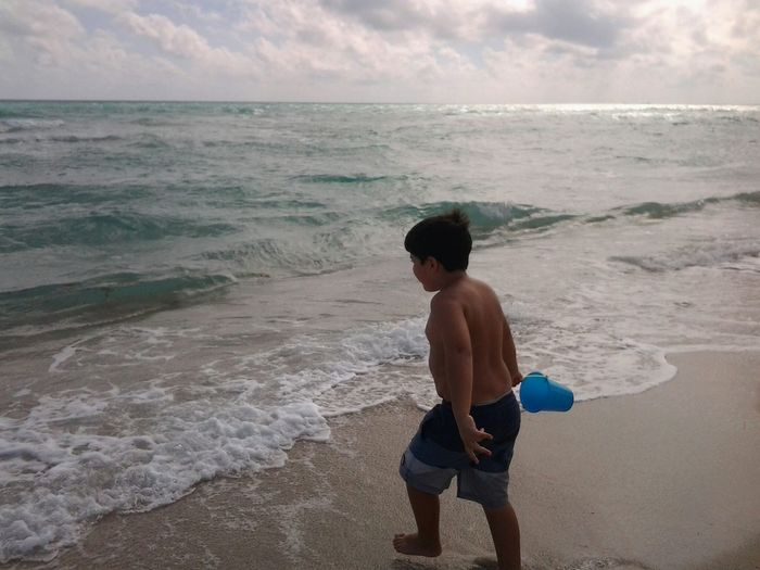 Full length of shirtless boy with bucket walking at beach