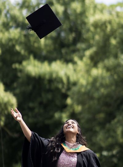 Woman throwing mortarboard in air against trees