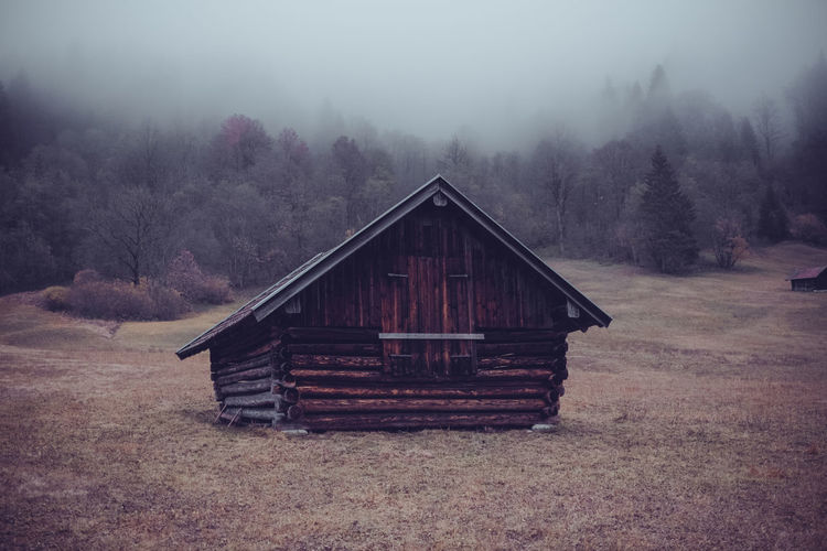Wooden house on field against trees in forest