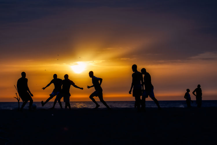 Boys playing football at Sunset on the lagoon of Somone