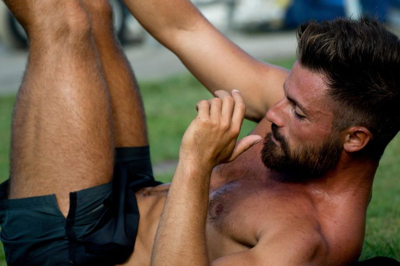 Close-up of shirtless man exercising in lawn