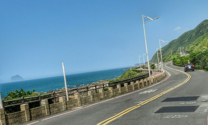 Car on coastal road against sky