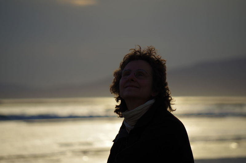Smiling woman at beach against sky