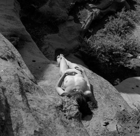 High angle view of man lying on rock