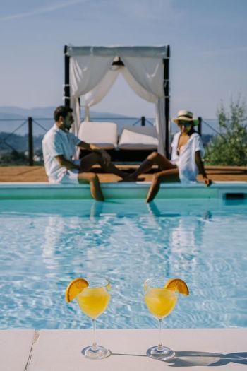 People relaxing in swimming pool against sky