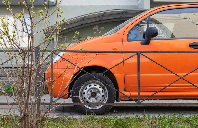 Vintage car parked against orange wall