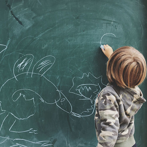 Rear view of boy drawing on blackboard at classroom