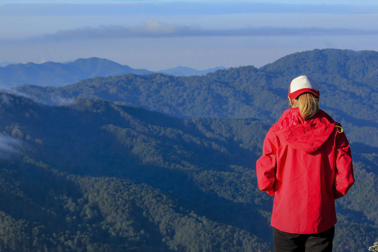 A woman wearing a red coat stands on a mountain view. Beauty In Nature Clothing Environment Hood - Clothing Idyllic Landscape Leisure Activity Lifestyles Looking At View Mountain Mountain Range Nature Non-urban Scene One Person Real People Rear View Scenics - Nature Three Quarter Length Tranquility Warm Clothing Winter