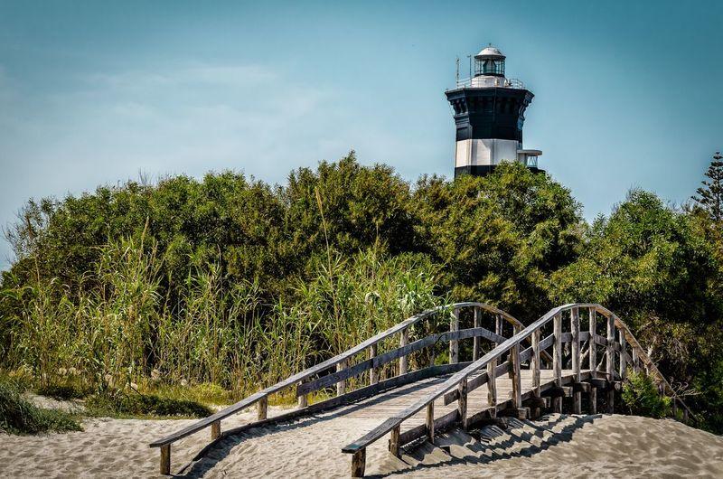 Footbridge by trees against lighthouse