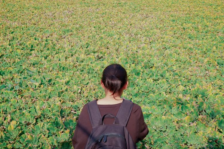 Rear view of teenage girl with backpack on grass